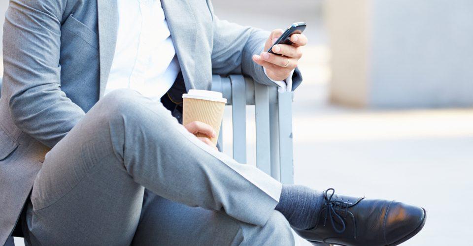 Joven ejecutivo mirando un móvil smartphone en la calle con un móvil en la mano, sobre la compra online e ecommerce