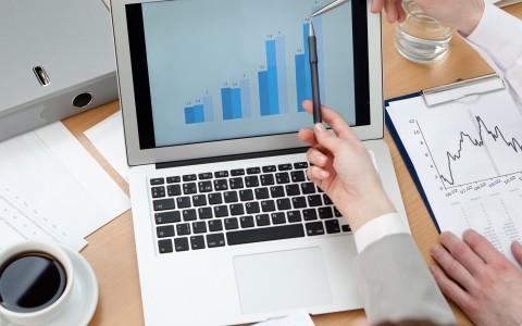 dos personas analizando datos en unordenador con gráficas de seguimiento de distintos segmentos de clientos en una base de datos