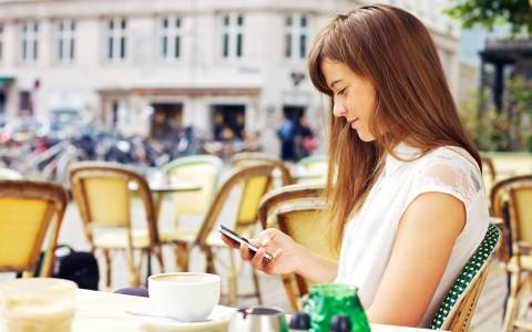 Millenials fidelización cabecera. Joven chica guapa sentada en una terraza en una plaza mientras navega en su móvil por internet