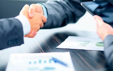 Mid-market colaboración entre Sage y Alxia Dos personas con traje se dan un apretón de manos mientras una tercera tiene una tablet en la mano y varias gráficas sobre la mesa