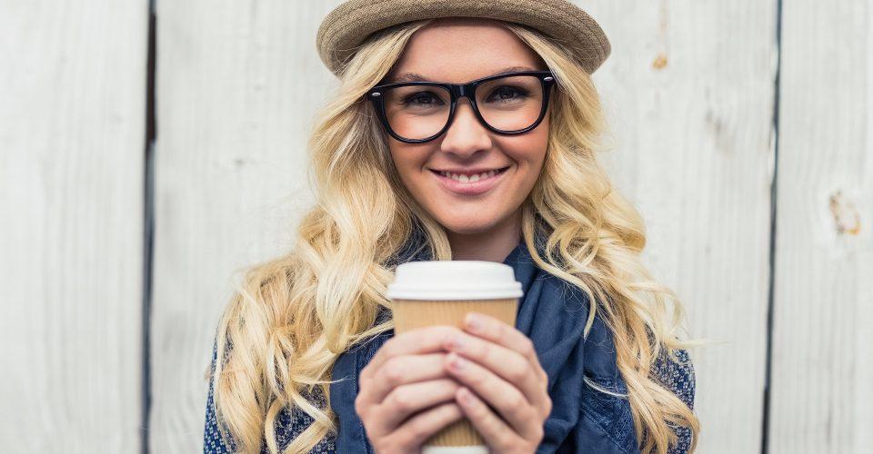 Sobre programas de fidelización Chica joven y moderna con sombrero y gafas sostiene en sus manos un vaso de café de papel del estilo Starbucsks