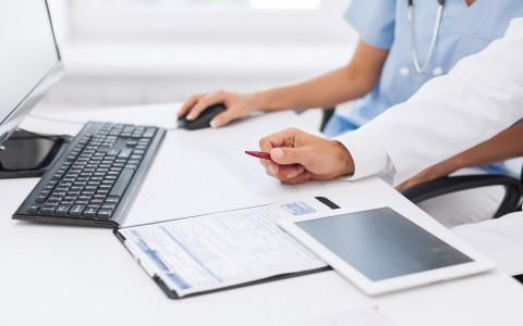 Big data sanitario, una enfermera y un doctor revisan gráficas en el ordenador junto a una tablet y una gráfica en papel