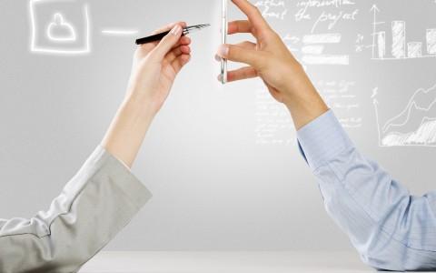 Sobre un fondo gris luminoso aparece el brazo de una mujer escribiendo con un lapicero digital sobre un móvil que sujeta el brazo de un hombre. Flotando aparecen gráficas en color blanco