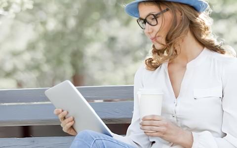 una atractiva joven mira sonriente una tablet digital sentada en el banco de un parque, con un sombrero en la cabeza y un vaso de café en la mano