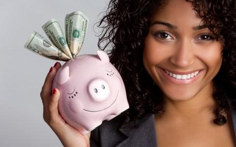 micliente | servicios al cliente sector bancario | Una atractiva mujer con el pelo rizado y la piel color canela sostiene una hucha con algunos billetes