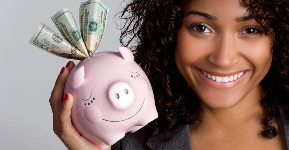 micliente   servicios al cliente sector bancario   Una atractiva mujer con el pelo rizado y la piel color canela sostiene una hucha con algunos billetes